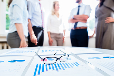 Business people in office with financial data on desk ready for analysis